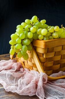 Raisins verts dans une boîte en bois, sur un tissu