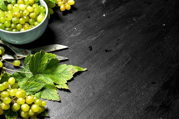 Raisins verts dans un bol avec des feuilles sur tableau noir.