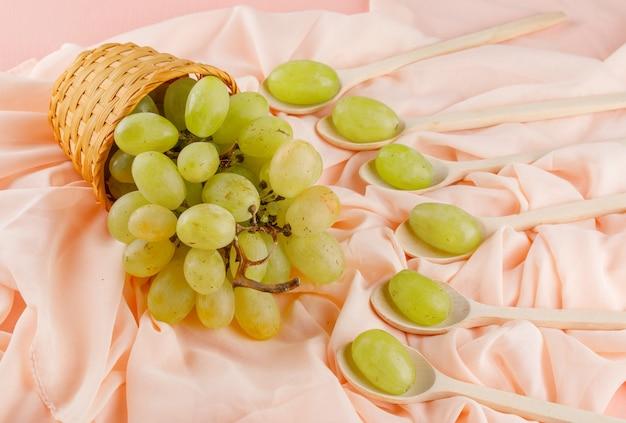 Raisins verts dans des cuillères en bois et panier sur rose et textile. vue grand angle.