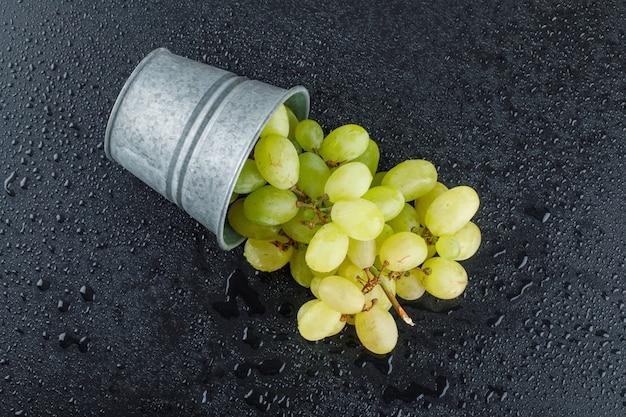 Raisins verts épars d'un mini seau sur un gris foncé.