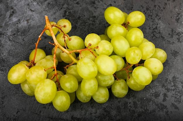 Raisins verts sur fond de marbre foncé. cave volumétrique. une grappe de raisin vert.