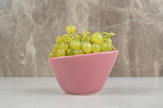 Raisins verts frais dans un bol rose