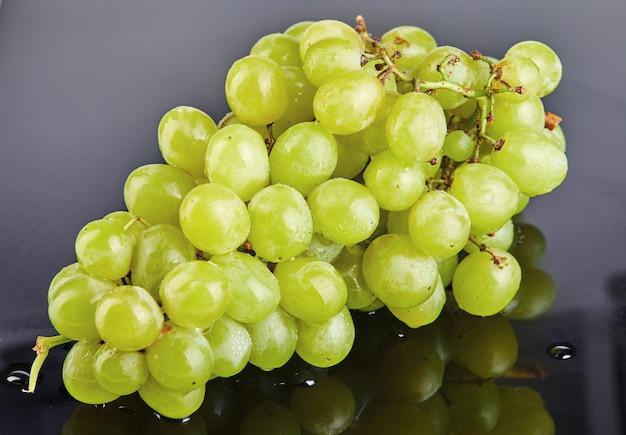 Raisins verts frais avec de l'eau tombe sur un fond gris