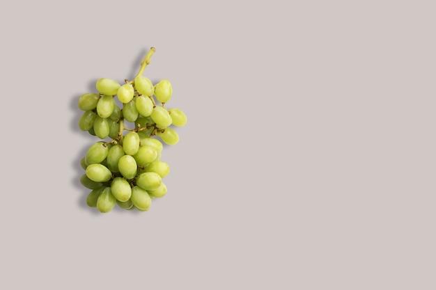 Raisins verts frais sur fond blanc pour le menu. fond géométrique. mise à plat, espace de copie, vue de dessus.