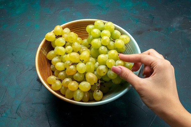 Raisins verts frais à l'intérieur de la plaque sur un bureau bleu foncé