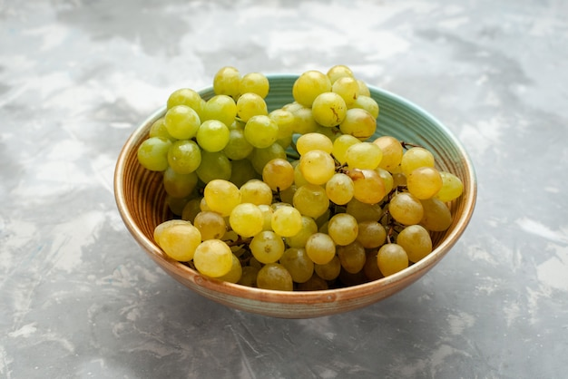 Raisins verts frais à l'intérieur de la plaque sur la lumière