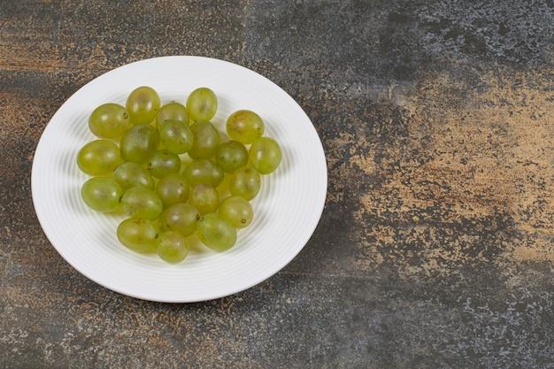 Raisins verts frais sur plaque blanche.