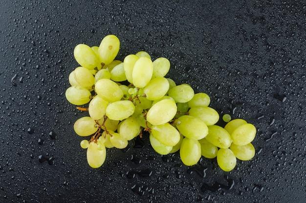 Raisins verts sur un gris foncé.