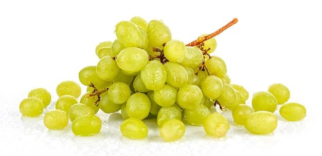 Raisins verts humides avec des gouttes d'eau sur une surface brillante sur fond blanc