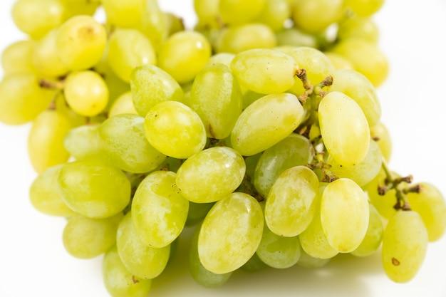 Raisins verts mûrs sur fond blanc. baies juteuses sucrées. produits bio de la ferme