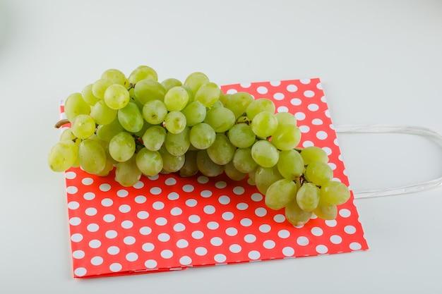 Raisins verts sur sac blanc et papier. vue grand angle.