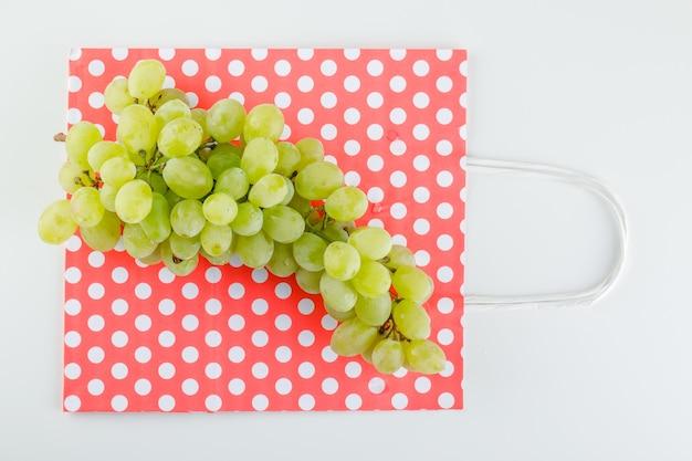 Raisins verts sur sac blanc et papier.
