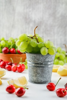Raisins verts avec des tranches de citron, des cerises dans un mini seau et un bol sur une surface blanche