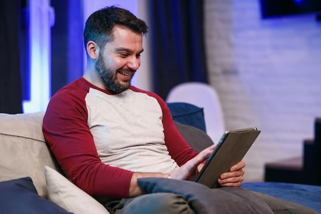 Ralenti d'un homme de 30 ans moderne et sympathique avec une barbe bien entretenue qui repose sur le canapé à la maison et qui parcourt les applications sur tablette avec un sourire chanceux