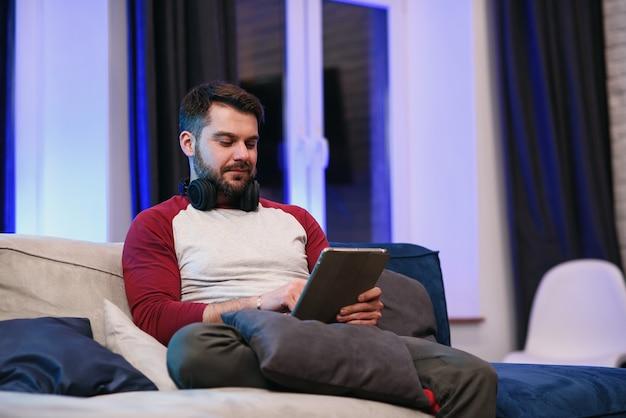 Ralenti d'un homme de 30 ans moderne et sympathique avec une barbe bien entretenue reposant sur le canapé à la maison et parcourant les applications sur tablette avec un sourire chanceux