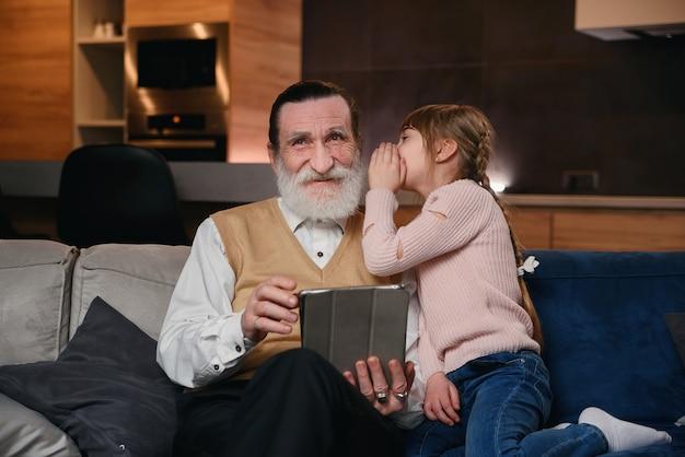 Ralenti de jolie fille joyeuse de 12 ans avec des nattes drôles qui chuchotant à l'oreille de grand-père son secret alors qu'ils étaient assis ensemble sur le canapé à la maison