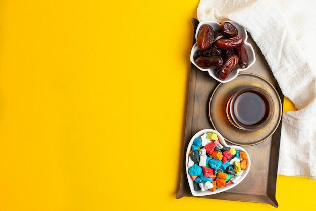 Ramadan kareem festival, dates sur le bol avec une tasse de thé noir et des bonbons colorés