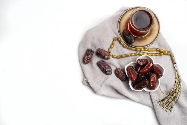 Ramadan kareem festive, gros plan de dattes sur un bol et une tasse de thé noir