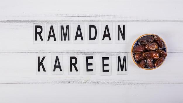 Ramadan kareem text avec bol de dattes juteuses sur le bureau blanc
