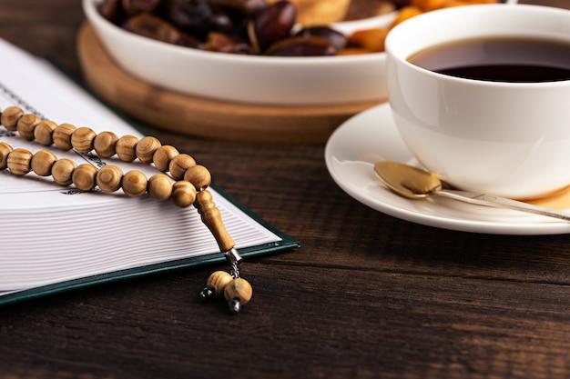 Ramadan, tasse de thé gros plan, assiette de fruits secs, chapelet en bois, coran sur fond en bois brun, concept iftar