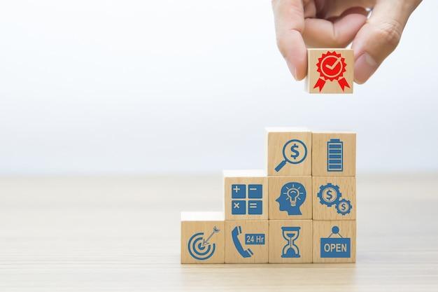 Ramasser à la main le symbole de la qualité sur un bloc de jouets en bois.