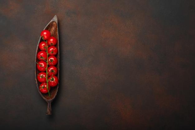 Rameau de tomates cerises sur une plaque en bois et fond brun rouillé