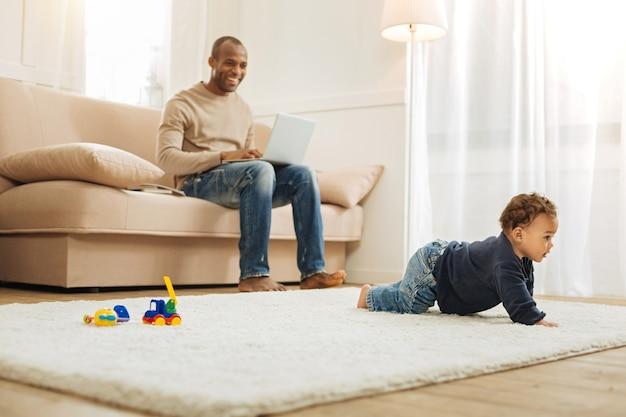 Rampant. prendre soin de jeune père afro-américain souriant travaillant sur son ordinateur assis sur le canapé et regardant son petit-fils ramper