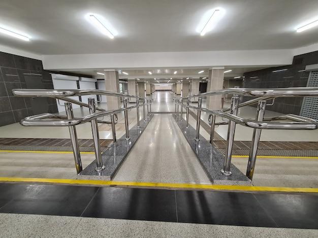 Rampe pour handicapés avec garde-corps métalliques en arrière-plan du passage souterrain
