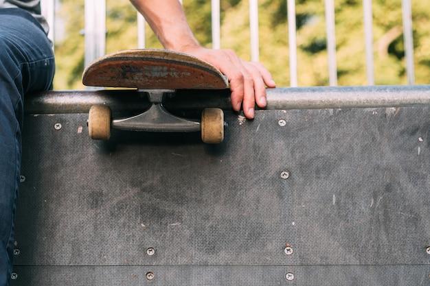 Rampe de skate park. sports extrêmes. la culture des jeunes. main de l'homme sur la planche à roulettes.