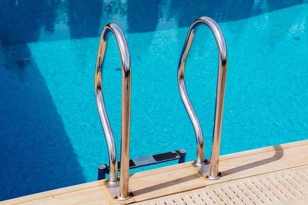 Les rampes de l'escalier menant à la piscine. fond avec des carreaux bleus. section baignade et vacances à la plage. installations de purification de l'eau dans la piscine.