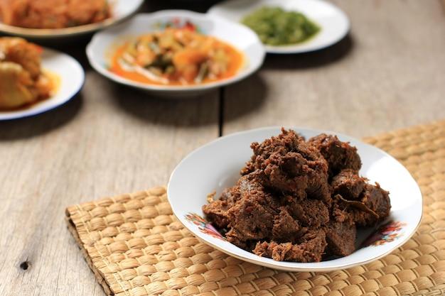 Randang avec divers plats de padang appelé masakan padang ou plats de padang sur fond. servir sur couche de plaque empilée sur fond rustique