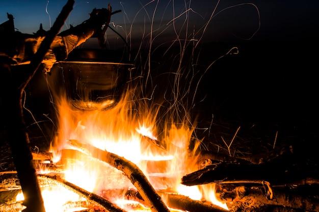 Randonnée dans la nature au coucher du soleil se préparant à une randonnée sur le bûcher éteindre le feu en plein air romance de wi ...