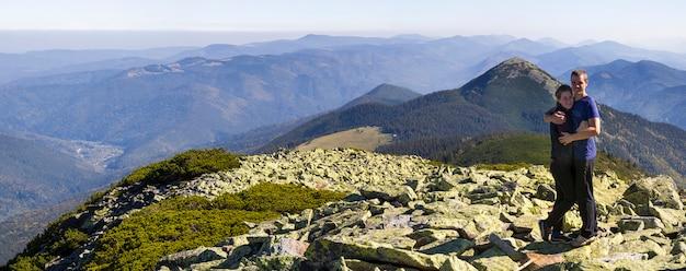 Randonnée de jeune couple dans les carpates. homme et femme debout au sommet de la montagne