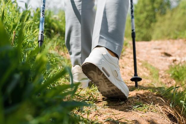 Randonnée pédestre dans la nature. gros plan sur des bottes blanches et des bâtons scandinaves escaladant une colline par une échelle. mode de vie sain et actif, randonnée en plein air.