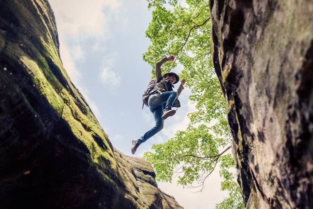 Randonnée pédestre de l'homme. faites un saut au-dessus d'une falaise abrupte.