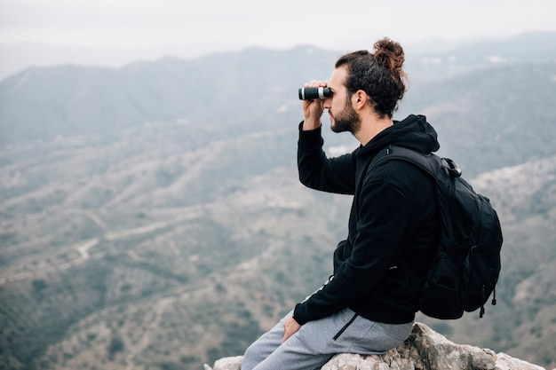 Randonneur, assis, sommet, rocher, regarder travers, jumelles, regarder, vue montagne