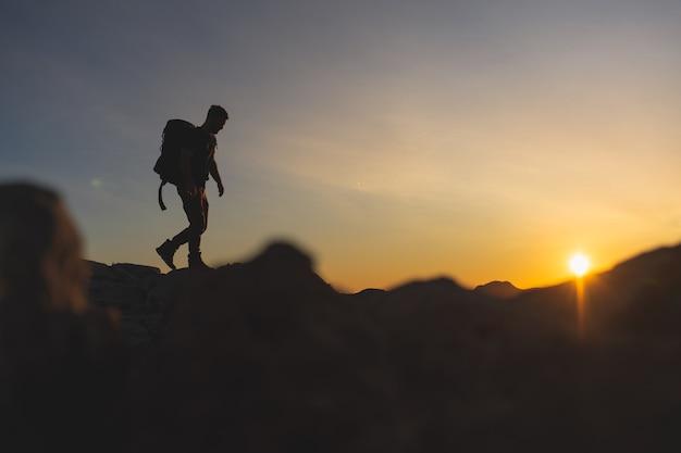 Randonneur au sommet d'une montagne marchant sur la crête de la montagne avec beau coucher de soleil heure d'or avec des couleurs intenses et un ciel bleu fusionné avec du jaune, portant un grand sac à dos