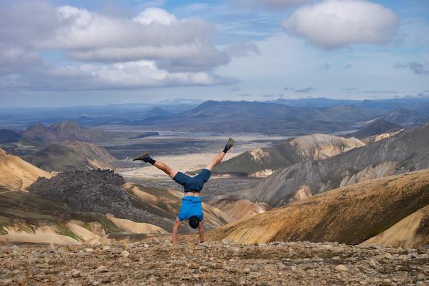 Randonneur debout sur sa main dans la vallée de landmannalaugar. islande. montagnes colorées sur le sentier de randonnée de laugavegur.