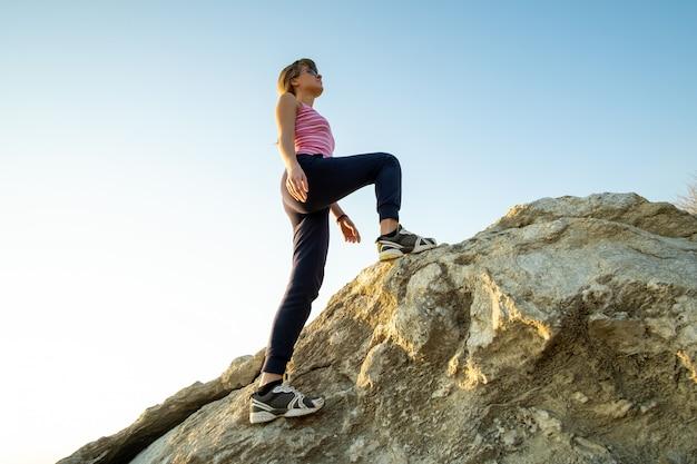 Randonneur escalade gros rocher sur une journée ensoleillée