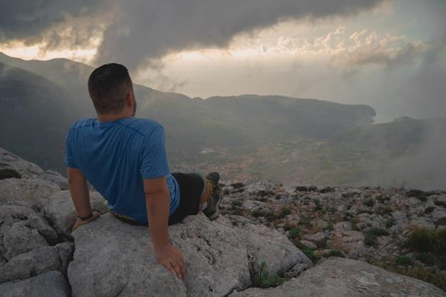 Le randonneur est assis sur un rocher tout en contemplant