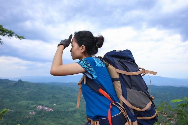 Randonneur femme asiatique réussie profiter de la vue sur le sommet de la montagne