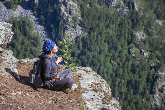 Randonneur femme assise au sommet d'une montagne et se détendre en journée d'été ensoleillée