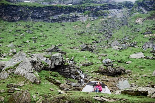 Randonneur femme assise près de sa tente de détente