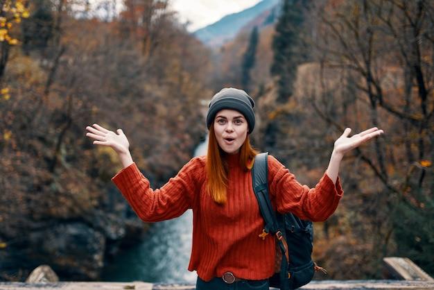 Randonneur femme émotionnelle près de la rivière joie voyage
