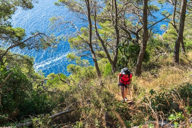 Randonneur femme escalade vers le phare de sant sebastian dans la ville de llafranc.