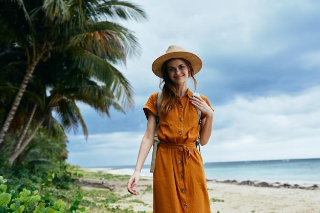 Randonneur de femme gaie sur les palmiers d'île de promenade de voyage de plage