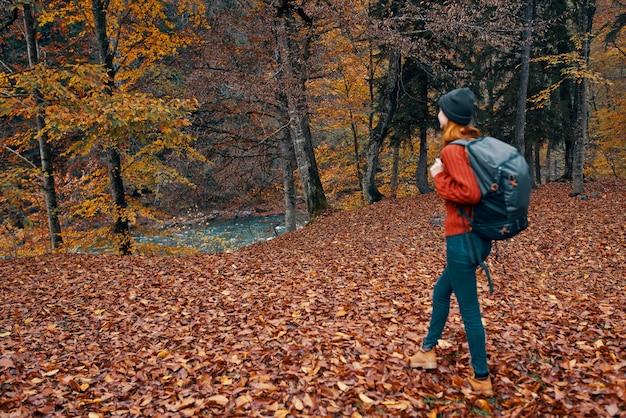 Randonneur de femme marchant dans l'air frais de voyage de forêt d'automne