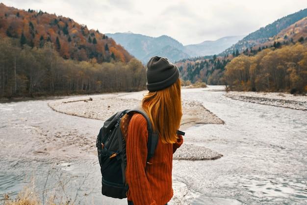 Le randonneur de femme marche près du voyage de nature de montagnes de rivière