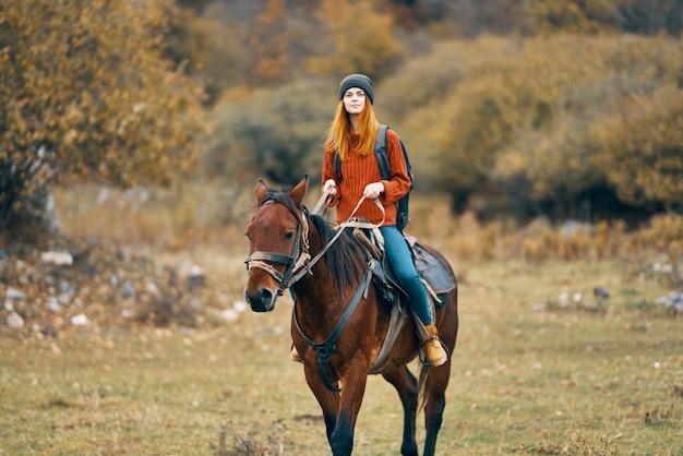 Randonneur femme monte un cheval dans un paysage nature montagnes champ