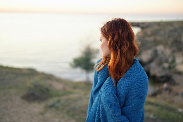 Randonneur femme en plaid bleu dans l'air frais du paysage des montagnes. photo de haute qualité